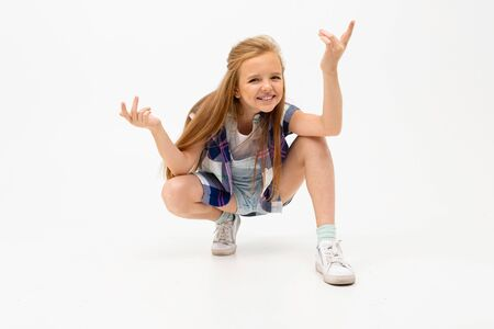 funny girl squatted and waves her hands on a white background.