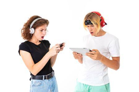 paar meisje en jongen spelen op tablet en telefoon op een witte achtergrond.
