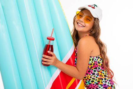 Caucasian tanned girl with a glass of drink and an air mattress for swimming on a white background.