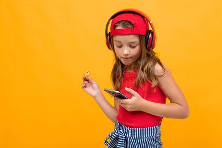 有耳机的逗人喜爱的迷人的女孩在黄色背景。