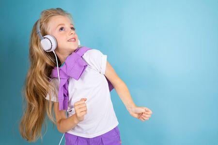 一个美丽的白肤金发的迷人的年轻逗人喜爱的甜微笑女孩画象有听到在浅兰的背景的音乐的白色大耳机的。
