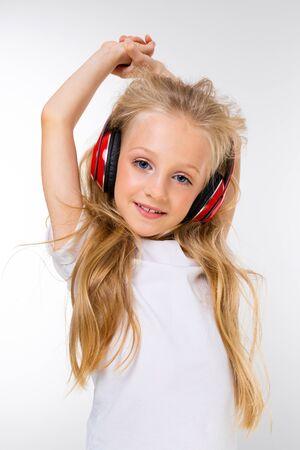 Retrato de una hermosa rubia encantadora niño lindo en un look casual con auriculares rojos escuchando música y sobre un fondo blanco.