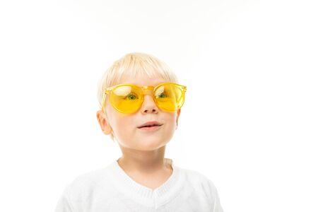 portrait d'un charmant garçon blond souriant à lunettes de soleil vêtu d'un T-shirt blanc sur fond de studio blanc.