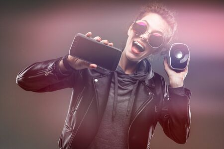 impudent girl in glasses with a portable speaker and a phone on a black background with glow effect.