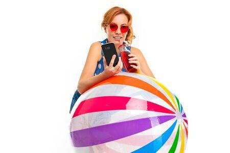 有一个可膨胀的球的女孩游泳,电话和一杯鸡尾酒在她的在白色背景的手上。