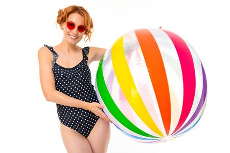 attractive girl in retro black one-piece swimsuit and sunglasses with a striped ball for water on a white background.