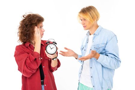 A couple in love with alarm clock argues about time isolated on white