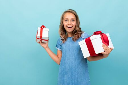 surprised happy girl with two boxes of gifts on a light blue background.
