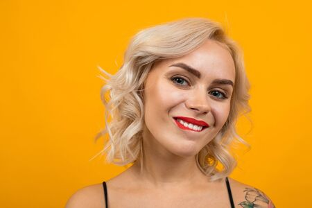 portrait of a glamorous blonde girl with beautiful make-up biting her lip and flirting on a yellow background.