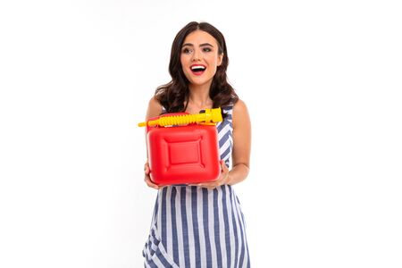 sexy girl in a dress holds a canister with fuel gasoline on a white background with copy space