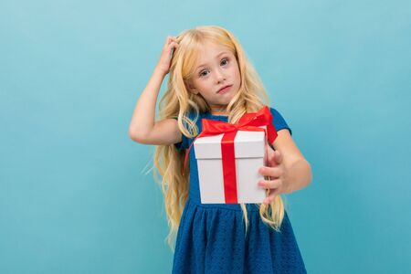 pensive cute blond girl in a dress with a gift in her hands on a light blue background.