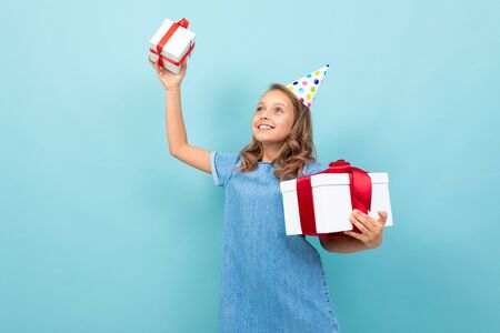 happy caucasian girl with holiday hat holding her presents on studio light blue background.