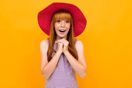 portrait of a red-haired attractive surprised tourist girl in a red summer straw hat on a yellow background with copy space.