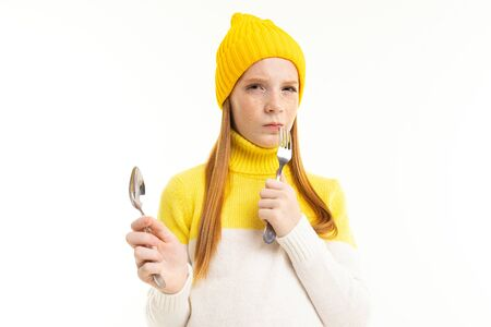 Happy teenager girl with red hair, hoody and hat holds a spoon and a fork isolated on white background.