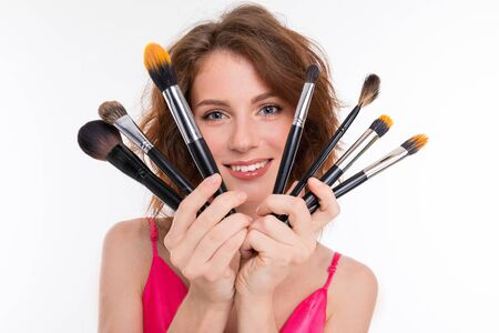 attractive girl holding a fan of a lot of makeup brushes on a white background. Archivio Fotografico - 137275627