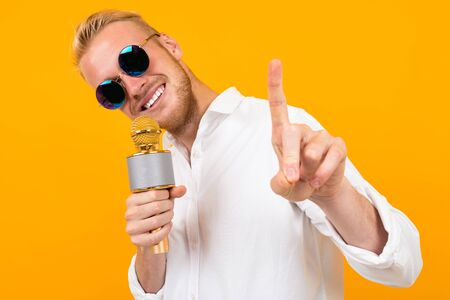 Fashionable caucasian male with glasses sings songs in karaoke isolated on yellow background