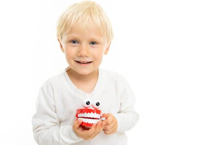 close-up of a blond male child with a toy in the form of a white tooth jaw on a white background with copy space.
