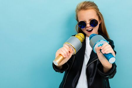 Young caucasian female with brown hair in black jacket, blue sunglasses sings songs with blue and yellow microphones isolated on blue background