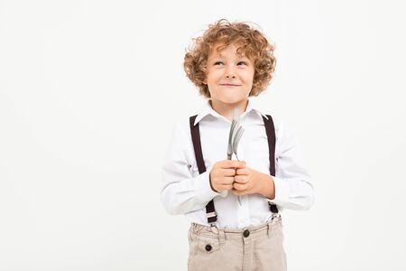 Beautiful boy with curly hair in white shirt, brown hat, glasses with black suspenders holds a knife and forks isolated on white background.