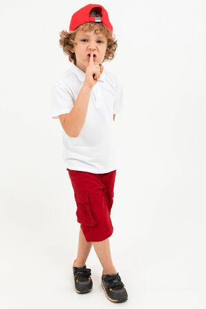 Caucasian boy in white t-shirt, red cap, red shorts advises to remain silent isolated on white background.