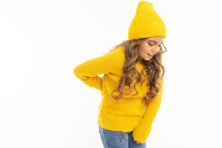 Happy caucasian girl in yellow hat and hoody have backache isolated on white background.
