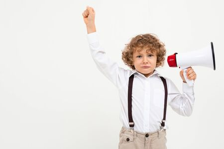 Beautiful boy with curly hair in white shirt, brown hat, glasses with black suspenders listening throung a megaphone isolated on white background.