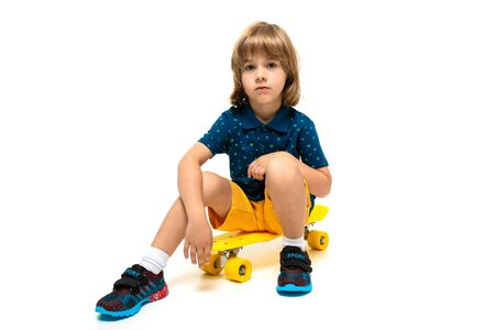 young european cute child in sportswear sitting on a yellow skateboard on a white background. Banco de Imagens
