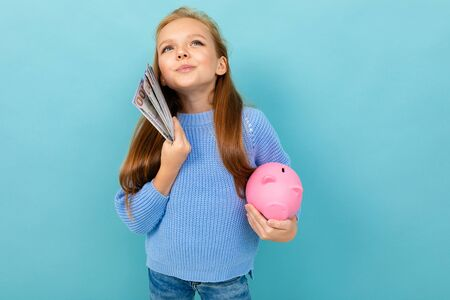 Portrait of little caucasian girl with long brow hair in blue hoody holds pink pig moneybox with a lot of money isolated on blue background Banco de Imagens