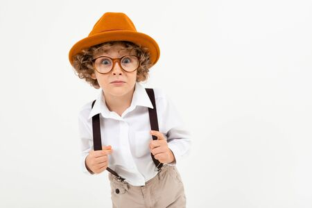 Beautiful boy with curly hair in white shirt, brown hat, glasses with black suspenders stands isolated on white background. Banco de Imagens