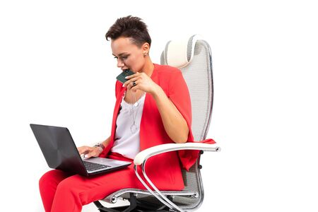 Beautiful woman in red office suit with short dark hair makes an important meeting and works with laptop, sits on a chair.