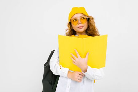 stylish caucasian charming girl in a white shirt, with a hat and a backpack with a notebook in her hands on a white background.