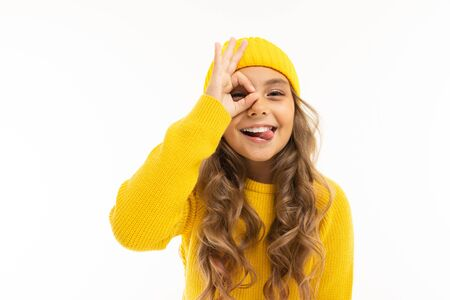 attractive beautiful girl in a yellow winter hat grimaces on a white background. Banco de Imagens