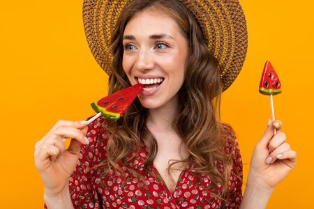 lovely charming girl close-up, lady with watermelon-shaped lollipops on a yellow background.