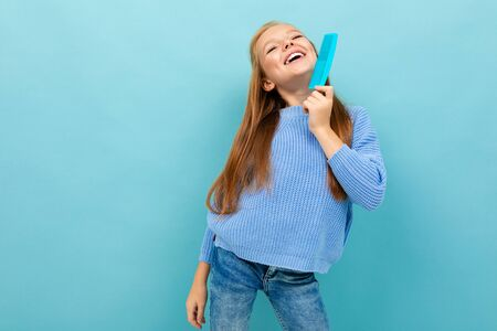 Beautiful caucasian teenager girl with brown hair in blue hoody brushes her hair with blue comb isolated on blue background