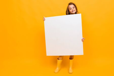 surprised girl holding a billboard with a mockup on a yellow background with copy space.