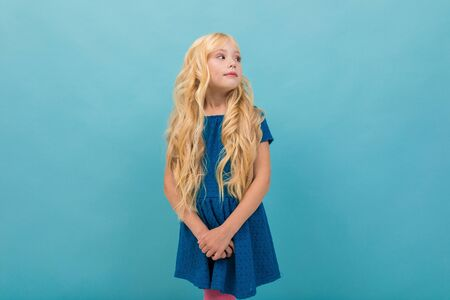 Little caucasian girl in blue dress with long blonde hair isolated on blue background.