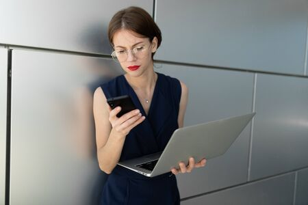 attractive charming young business woman with red lips with a laptop in her hands leans against the wall of the office center of the building and makes an appointment by phone. Banco de Imagens
