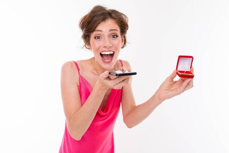 lovely caucasian girl with a box with a ring in her hands calls on a telon and reports joy on a white background.