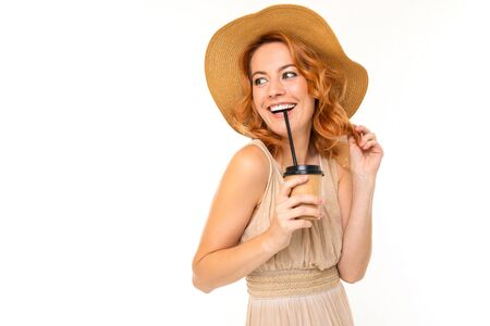 smiling stylish girl in a summer dress with a straw hat holds a cup of coffee on a white background with copy space.