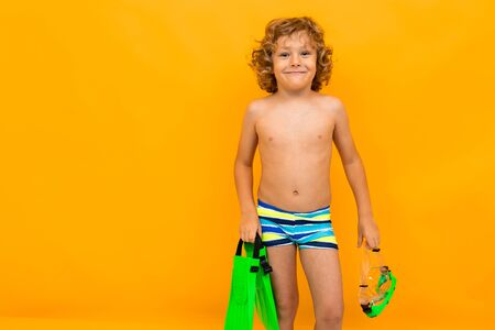 Little boy with curly hair in swimsuit with fins and goggles for swimming isolated on yellow background.