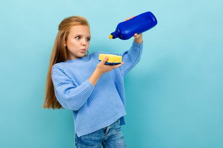 Girl is going to wash the dishes with washcloth and detergent isolated on blue background.