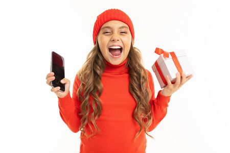 Caucasian girl in red hoody and hat holds a white box with gift in one hand and a smartphone in other hand, smiles and choises between it isolated on white background