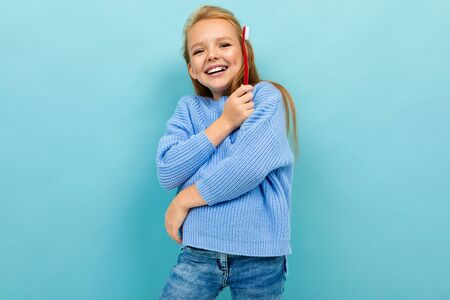 Teenager girl with tooth brush recommends brushes teeth, isolated on blue background Banco de Imagens