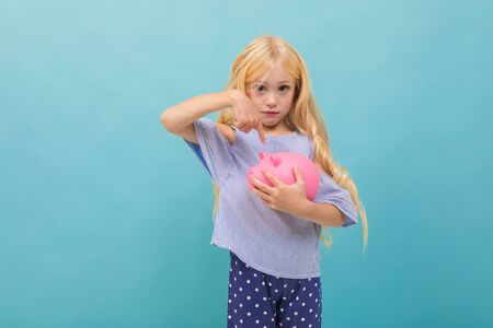 Portrait of little caucasian girl in blue t-shirt with long blonde hair holds pink pig moneybox isolated on blue background.