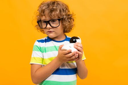Little boy with curly hair in colourful t-shirt and shorts holds a toy isolated on yellow background. Banco de Imagens