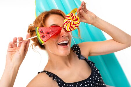 portrait of a girl with retro sunglasses with lollipops on the background of a surfboard.