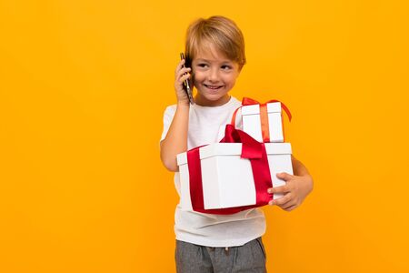 Caucasian boy holds many white boxes with gifts and rejoices, portrait isolated on yellow background. Banco de Imagens