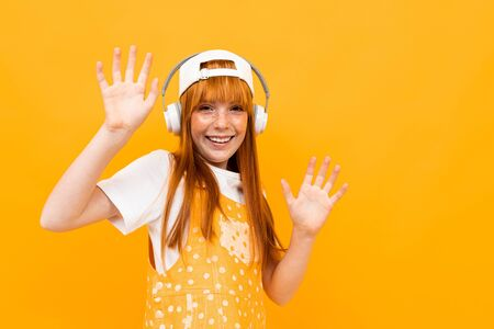 Happy teenager girl with red hair, orange hoody and hat with credit card and phone isolated on white background.