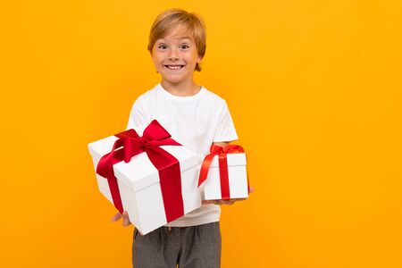 holiday concept. attractive boy holds out a box with a gift with a red ribbon on a bright yellow background.