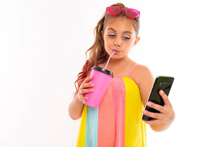 colorful portrait of a girl tourist resting with a swimming ball and a phone with a mockup on a white background.